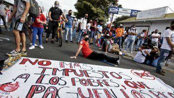 La gente se manifiesta junto a un cartel que dice No más impuestos a los pobres, haz que los ricos paguen, contra la moción del gobierno de aumentar los impuestos para llegar a un acuerdo crediticio con el Fondo Monetario Internacional (FMI), frente a la casa presidencial en San José, el 12 de octubre de 2020.