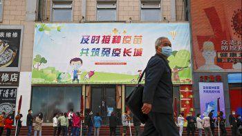 Un hombre con mascarilla para combatir los contagios de coronavirus pasa junto a personas con mascarilla que hacen fila para vacunarse contra el COVID-19 en un centro de vacunación con el lema Una vacunación oportuna para construir juntos la Gran Muralla de la Inmunidad, en Beijing, el miércoles 21 de abril de 2021.