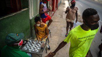 Personas con máscaras como precaución contra la propagación del nuevo coronavirus caminan por una calle mientras otros juegan al ajedrez en una acera en La Habana, Cuba, el miércoles 23 de septiembre de 2020. Estados Unidos agregó el lunes 28 de septiembre de 2020 a su lista negra para operar con Cuba a una tarjeta de débito que en los últimos meses se volvió popular en la isla porque les permite a los ciudadanos comprar electrodomésticos, piezas de repuestos y alimentos.
