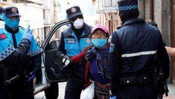 La policía metropolitana detiene a una vendedora de fruta callejera, lo cual está prohibido debido al coronavirus, en Quito, Ecuador, el viernes 10 de abril de 2020.