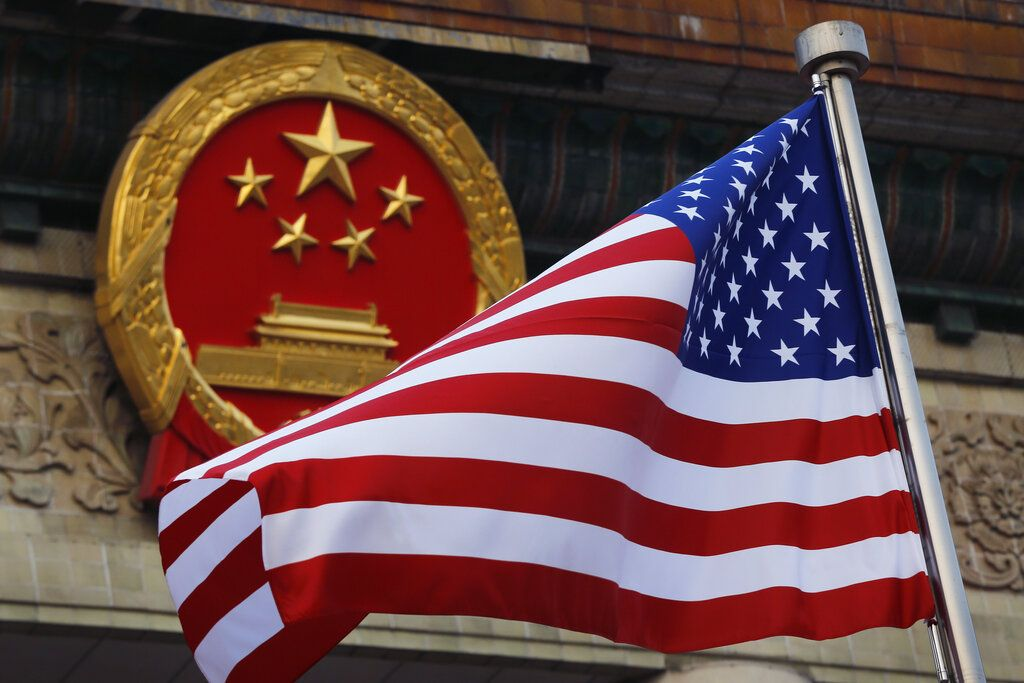 Una bandera estadounidense junto al emblema nacional de China en una ceremonia de bienvenida a visitantes estadounidenses.