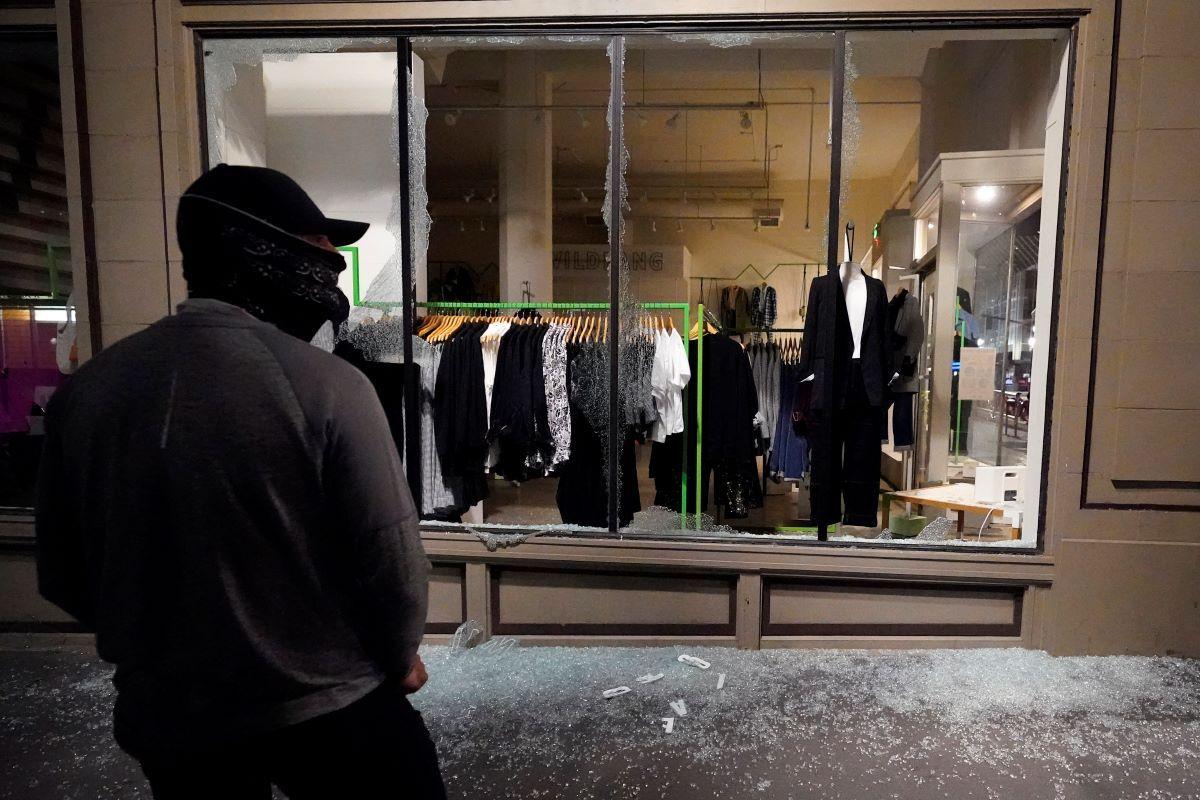 Un hombre permanece frente a un escaparate roto en una tienda durante protestas en Portland, Oregon.