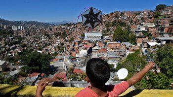 """Un niño vuela una cometa durante la conmemoración del 400 aniversario del barrio Petare de Caracas, el 17 de febrero de 2021. Se volaron 400 cometas durante un evento organizado por la fundación """"Alimenta la Solidaridad""""."""