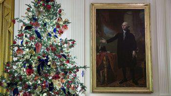 Un árbol de Navidad aparece al lado de un cuadro del expresidente George Washington en el Salón Este de la Casa Blanca, el lunes 2 de diciembre del 2019.