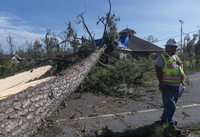 Un empleado de una compañía de electricidad examina los daños causados a las líneas eléctricas junto a un árbol grande que cayó sobre una casa después del paso del huracán Laura en Lake Charles el 27 de agosto de 2020.