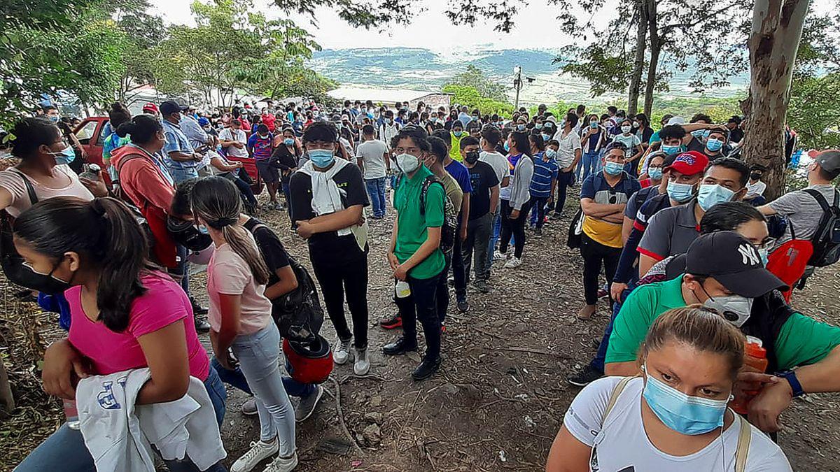 Hondureños y nicaragüenses hacen cola para vacunarse con las vacunas Pfizer-BioNTech y Moderna contra la enfermedad del nuevo coronavirus, COVID-19, en Guasaule, Honduras, en la frontera entre los dos países.
