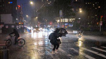 Peaones cubriéndose en la calle cerca de Columbus Circle, en la ciudad de Nueva York, el miércoles 1 de septiembre de 2021, al paso de los restos del huracán Ida.