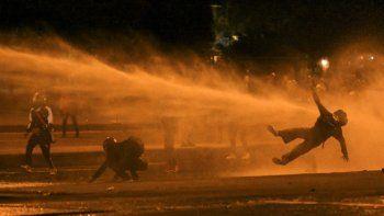 Un manifestante cae al ser alcanzado por un cañón de agua durante los enfrentamientos con la policía antidisturbios en medio de las continuas protestas contra el gobierno del presidente colombiano Iván Duque en Bogotá el 12 de junio de 2021.