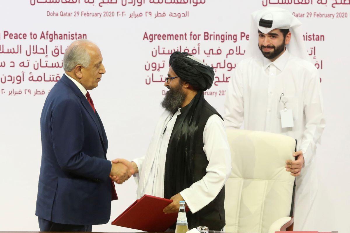 El enviado estadounidense Zalmay Khalilzad, izquierda, y el jefe político del Talibán, mulá Abdul Ghani Baradar, se estrechan la mano después de firmar el acuerdo de paz entre el Talibán y Estados Unidos en Doha, Qatar, sábado 29 de febrero de 2020