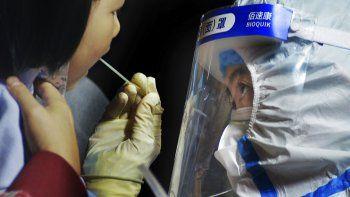 Un trabajador sanitario toma una muestra a un niño cerca de una zona residencial en Qingdao, en la provincia de Shandong, en el este de China, el 13 de octubre de 2020