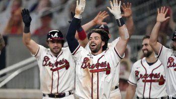 El torpedero de los Bravos de Atlanta Dansby Swanson, al centro, celebra su jonrón de dos carreras para ganar el juego en la novena entrada ante los Nacionales de Washington, el lunes 17 de agosto de 2020, en Atlanta.