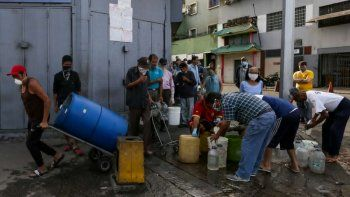 Personas usan mascarillas y pañuelos como medida preventiva contra la pandemia mundial de coronavirus COVID-19, mientras recolectan agua de una tuberíaen una calle en Caracas, Venezuela, el 21 de marzo de 2020.