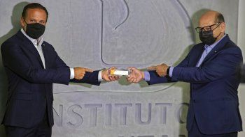 El gobernador del estado de Sao Paulo João Doria, izquierda, y el director del Instituto Butantan, Dimas Covas, sostienen una caja de una vacuna experimental contra el COVID-19 que está siendo sometida a pruebas en sociedad con la farmacéutica china Sinovac, durante una conferencia de prensa el lunes 9 de noviembre de 2020, en Sao Paulo, Brasil.
