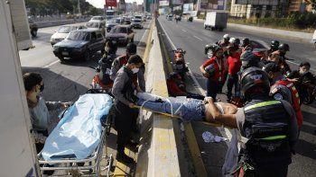 Scorristas voluntarios de la agrupación Ángeles de las Vías trasladan en camilla a un individuo herido en un accidente de motocicleta en Caracas el 10 de febrero del 2021.