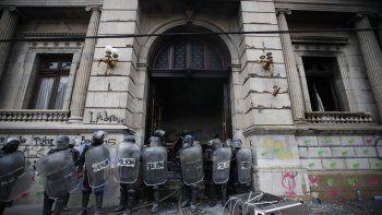 La policía antimotines forma un cordón mientras salen llamas de la sede del Congreso después de que manifestantes incendiaran una parte del edificio, el sábado 21 de noviembre de 2020, en Ciudad de Guatemala.