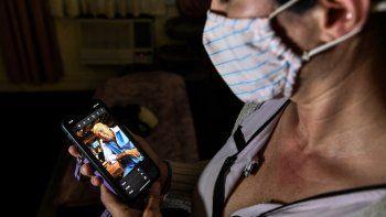 Ariane Gutiérrez mira una foto de su padre Gerardo Gutiérrez, quien murió a los 70 años el 28 de abril de 2020, luego de una batalla de un mes con COVID-19, en Miami Beach, el 20 de febrero de 2021.