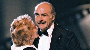 En esta foto de archivo tomada el 7 de marzo de 1987, el actor británico Sean Connery, presidente de la XII edición de los Premios César de la Academia Francesa, guiña un ojo al fotógrafo mientras baila en París con la actriz francesa Jeanne Moreau, en la ceremonia anual de premios de la industria cinematográfica francesa.