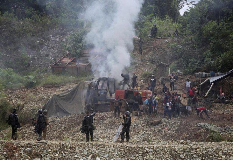 Mineros de oro intentan apagar un incendio en una maquinaria mientras soldados montan guardia cerca como parte de una operación de las Fuerzas Armadas colombianas contra la minera de oro ilegal en Magüi Payán