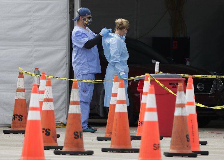 Trabajadores de la salud se ayudan mutuamente a colocarse equipo protector en un sitio de testeo del coronavirus en Miami Gardens