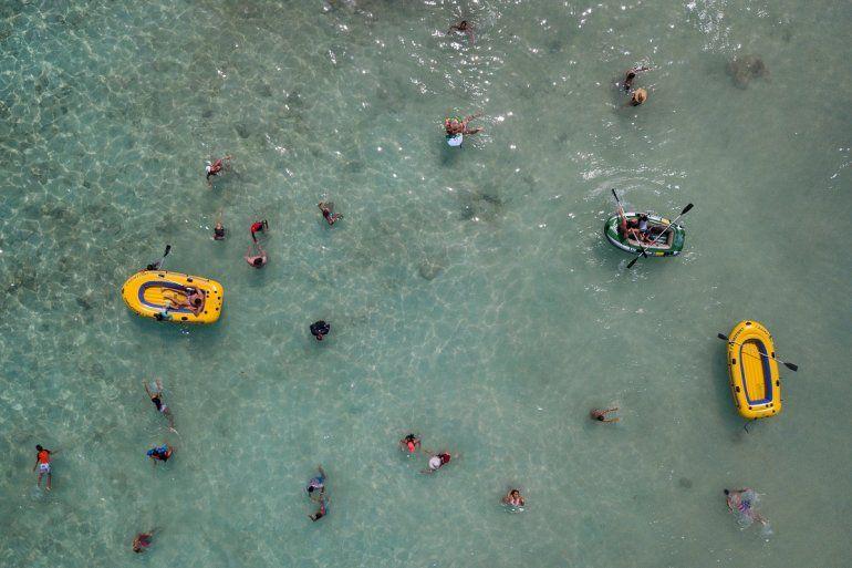 La gente nada y juega con botes en el Cayo Playuela del Parque Nacional Morrocoy