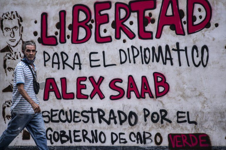 Un hombre pasa junto a un grafiti que dice Libertad para el diplomático Alex Saab