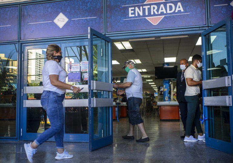 Gente con mascarillas en medio de la pandemia del nuevo coronavirus entra a una tienda de alimentos que acepta dólares estadounidenses en La Habana