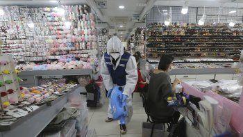 Un trabajador de salud rocía desinfectante en una tienda como precaución contra el nuevo coronavirus, en esta fotografía de archivo del 5 de febrero de 2020, en el mercado Namdaemun de Seúl.