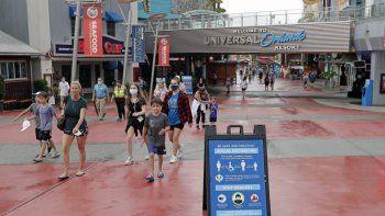 En esta foto del miércoles tres de junio de 2020, carteles sobre el distanciamiento social y otros protocolos reciben a los visitantes del Universal Orlando Resort en Orlando, Florida.