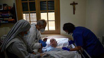 Félix Murillo, residente de la casa de ancianos El Buen Pastor (al centro), es asistido por el doctor Juan José Unzue y la enfermera Karen Oses mientras recibe la vacuna de Pfizer contra el coronavirus en Pamplona, España, el jueves 14 de enero de 2021.