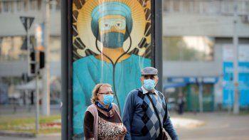 Ancianos con mascarillas pasan frente a una pintura de un empleado médico con equipo protector al estilo del Cristo Pantocrátor en Bucarest, Rumania, el miércoles 29 de abril de 2020.