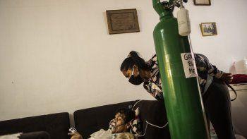 La hija de German Blanco, de 30 años, revisa a su padre mientras está acostado en un sofá en la sala de estar conectada a un tanque de oxígeno en su casa en Callao, Perú, el 4 de febrero de 2021. En Perú, con una población de 33 millones y más de 1,14 millones de personas infectadas, las muertes diarias se duplicaron a más de un centenar a finales de enero. Desde mayo, el país enfrenta una escasez de oxígeno médico que ha llevado a cientos de habitantes a hacer cola hasta 72 horas, durmiendo en las calles, para comprar este gas que el gobierno ha declarado recurso estratégico.