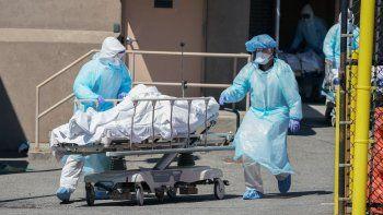 Personal de salud trasladan los cadáveres a un camión de refrigeración que sirve como morgue temporal en el Hospital Wyckoff en el distrito de Brooklyn, el 6 de abril de 2020 en Nueva York.