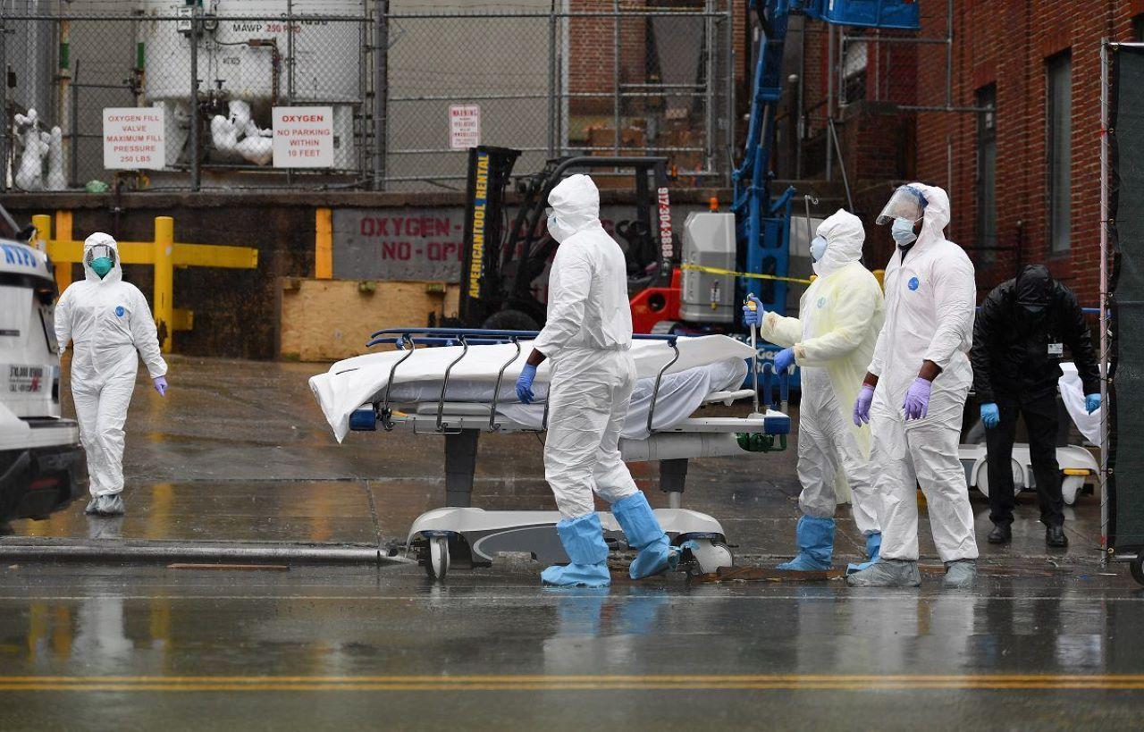 Paramédicos trasladan a uno de los fallecidos por COVID-19 a la morgue.