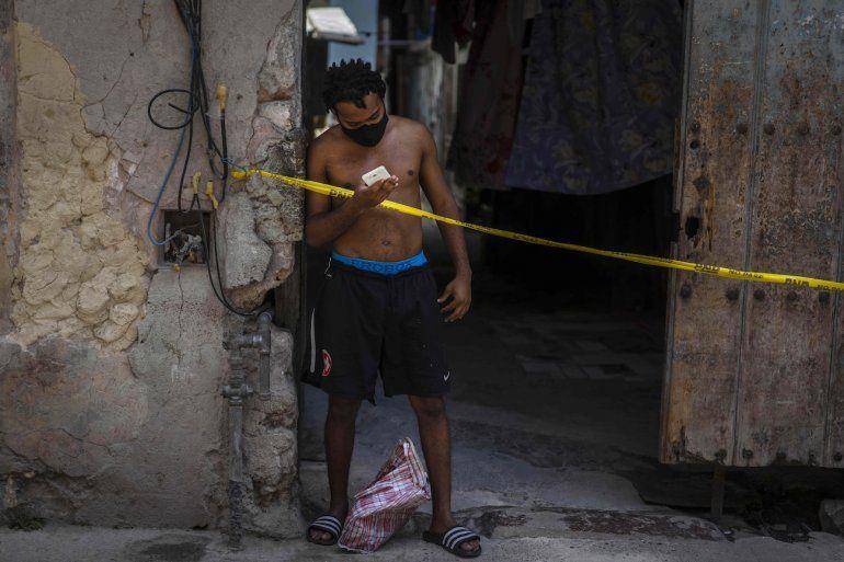 Un hombre que usa una máscara como precaución contra la propagación del nuevo coronavirus mira su teléfono inteligente desde la entrada de su casa en cuarentena en La Habana