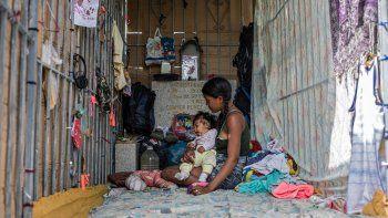 Una joven y un bebé descansan en un refugio improvisado en el cementerio general del sur de Caracas, el 16 de febrero de 2021. Las tumbas profanadas se han convertido en el hogar de muchas personas sin hogar en Venezuela.