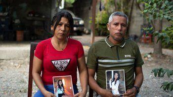Mileidys Torrealba (izquierda), 39, y Eduard José Falcón, 45, posan con retratos de su hija Eduarlis Falcón, de 20 años, quien fue asesinada junto a otra niña, en su casa en La Misión, estado Portuguesa, Venezuela el 27 de febrero. , 2021. Activistas de derechos humanos han advertido que la pandemia COVID-19 ha agravado la violencia de género a nivel mundial, con 256 feminicidios en 2020 en Venezuela, en comparación con 167 en 2019.