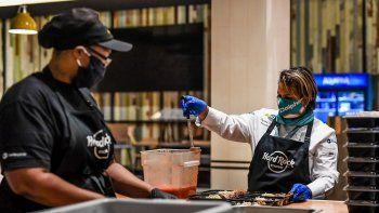 Cumpliendo contodos los protocolos de seguridad, la chef dominicana Dayanny de la Cruz (der.) sirve raciones para el Programa de ayuda alimentaria de los Dolphins de Miami.