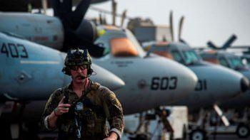 El técnico de eliminación de artefactos explosivos de tercera clase Ethan Tews cruza la cubierta de vuelo del portaaviones Ronald Reagan para abordar un helicóptero MH-60S SeaHawk y partir rumbo a un petrolero que fue atacado frente a las costas de Omán, en el Mar Arábigo.