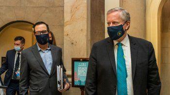 El jefe de despacho de la Casa Blanca Mark Meadows (derecha) y el secretario del Tesoro Steven Mnuchin llegan a la oficina de la presidenta de la Cámara de Representantes Nancy Pelosi en el Capitolio en Washington para reanudar sus conversaciones sobre un enorme proyecto de ley de alivio por la pandemia de COVID, el sábado 1 de agosto de 2020.