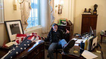 Richard Barnett, sentado en la oficina de la presidenta de la Cámara de Representantes, Nancy Pelosi, mientras protesta dentro del Capitolio de Estados Unidos en Washington, DC, el 6 de enero de 2021.