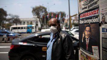 Un hombre usando mascarilla para protegerse del nuevo coronavirus pasa junto a un puesto de periódicos que muestra en primera plana al presidente Martín Vizcarra, afuera del Congreso en Lima, Perú, el viernes 11 de septiembre de 2020.