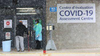 Un oficial de Salud Pública de Ottawa (derecha) habla con la siguiente persona en la fila en el centro de pruebas COVID-19, el 23 de marzo de 2020 en Ottawa, Canadá.