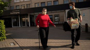 Diane Wanten (izq) sale del hospital donde ganó una batalla con el coronavirus acompañada por su hijo Frederico en Hasselt, Bélgica, el 29 de abril del 2020. No hay que entregarse. Hay que darle pelea al virus, dice.