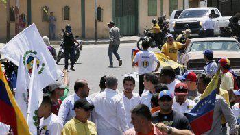 En esta fotografía difundida por la oficina de prensa de Juan Guaidó, un sujeto no identificado apunta con una pistola hacia un grupo de personas cuando el dirigente opositor, al centro con camisa azul claro, se reunía con partidarios en Barquisimeto, Venezuela, el sábado 29 de febrero de 2020.