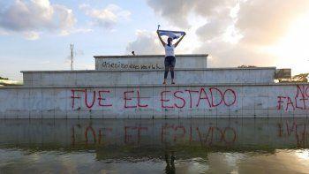 Un manifestante enmascarado alza una bandera durante una protesta contra el gobierno del presidente Daniel Ortega en Managua, Nicaragua. Se han presentado 18 testigos que dicen haber sufrido torturas y abuso sexual a manos de las fuerzas represivas, ante un panel de abogados y psicólogos en San José, Costa Rica, la semana del 11 de septiembre de 2020. Foto de archivo del 1 de junio de 2020.