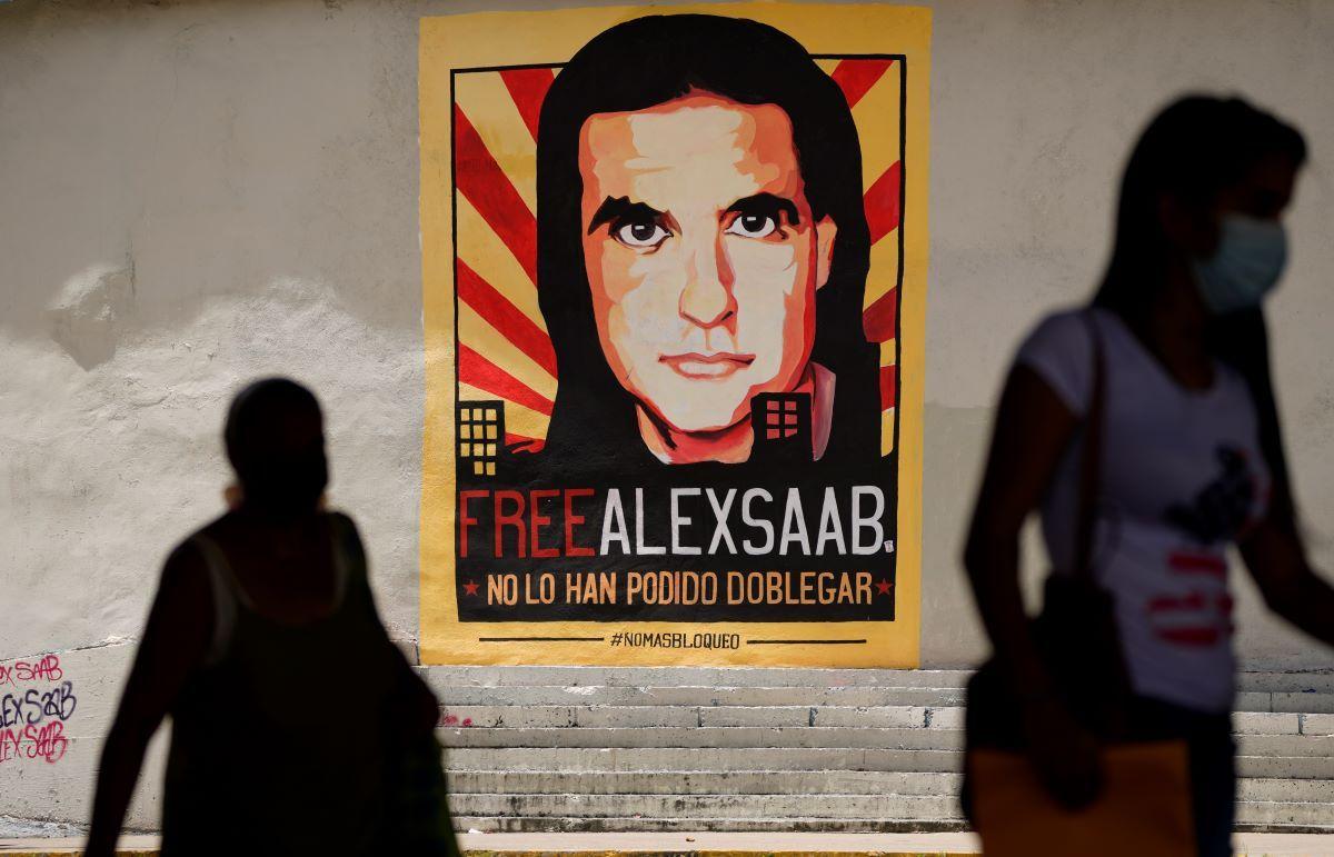 Personas caminan cerca de un cartel que pide la liberación del empresario colombiano, Alex Saab, en Caracas, Venezuela.