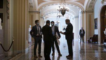 Personal del Congreso espera en un ornamentado pasillo en el exterior de la cámara del Senado durante una demora en los preparativos para acordar un paquete de ayudas por el COVID-19, en el Capitol, Washington, el 5 de marzo de 2021.