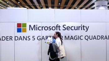 ARCHIVO - Una mujer camina frente a un módulo de Microsoft durante la Conferencia sobre Ciberseguridad, en Lille, Francia, el miércoles 29 de enero de 2020. (AP Foto/Michel Spingler)