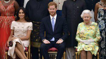El príncipeHarry, su esposa Meghan Markle (izquierda) y su abuela, la reina Isabel II, fotografiados durante una ceremonia en el Palacio de Buckingham el 26 de junio del 2018.