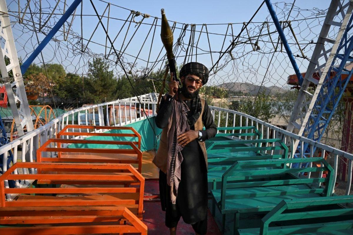 Un combatiente talibán que lleva un lanzagranadas propulsadas por cohete (RPG) se encuentra en un paseo en barco pirata en un recinto ferial en el lago Qargha en las afueras de Kabul.